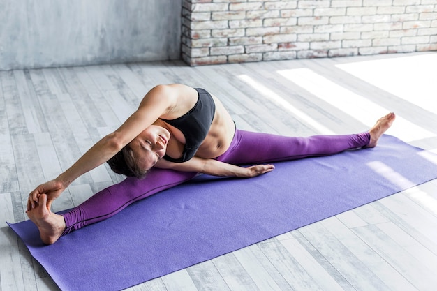Woman leaning over her shoulder while doing a split