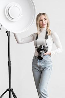 Женщина, опираясь на студийный светильник
