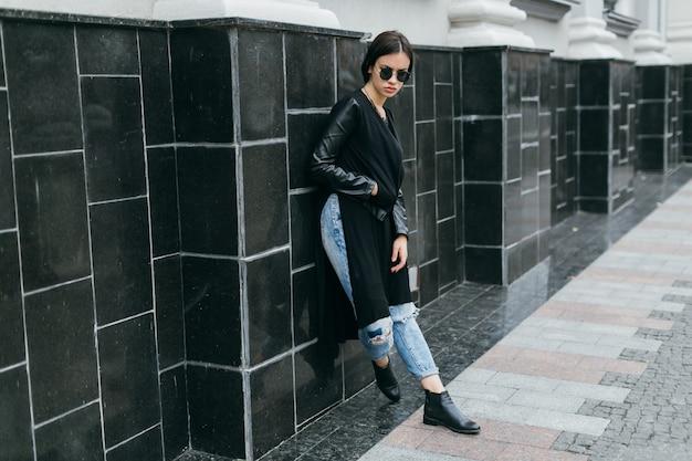 Женщина, опираясь на черную стену