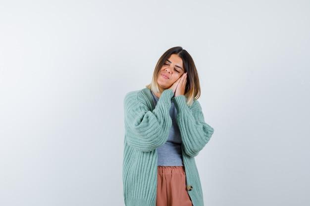 カジュアルな服装で枕のように手のひらに寄りかかって、平和に見える女性。正面図。