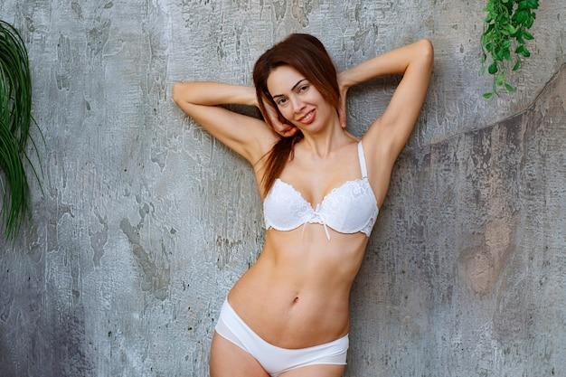 콘크리트 벽에 기대어 흰색 브래지어와 바지를 입고 포즈를 취하는 젊은 여성.