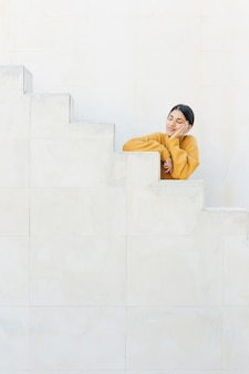 Woman leaning staircase with her eyes closed