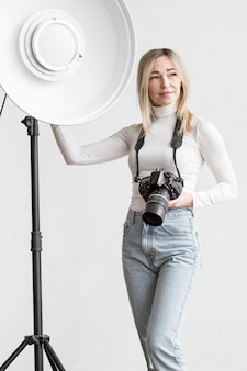 Woman leaning on a studio lamp