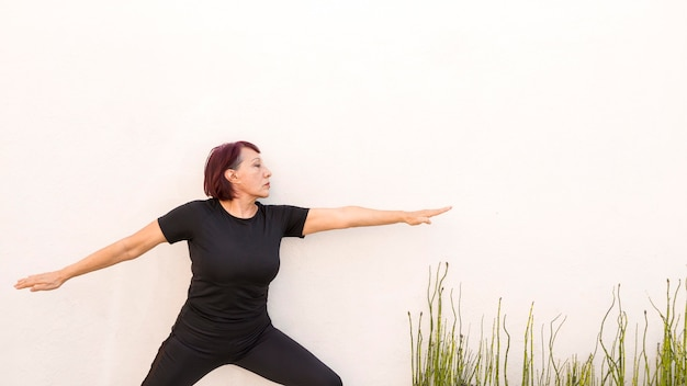 Woman leaning on a wall and doing exercises
