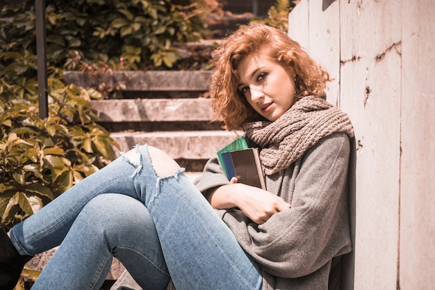 Woman leaning on wall and holding books