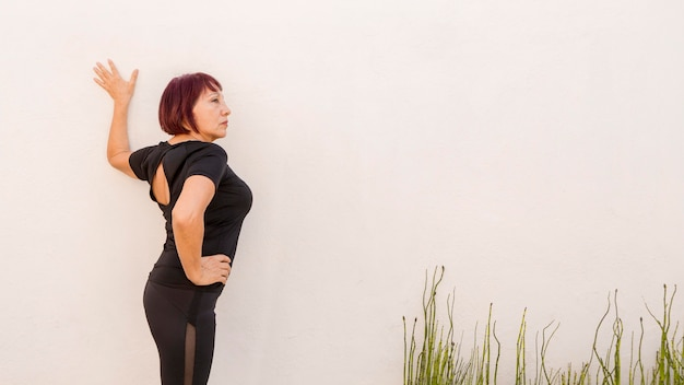 Woman leaning on a wall and stretching