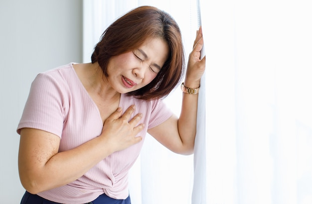 Woman leaning on wall with pain, suffer and distorted face and use hand to hold on the chest from heart disease. concept of st elevated myocardial infarction.