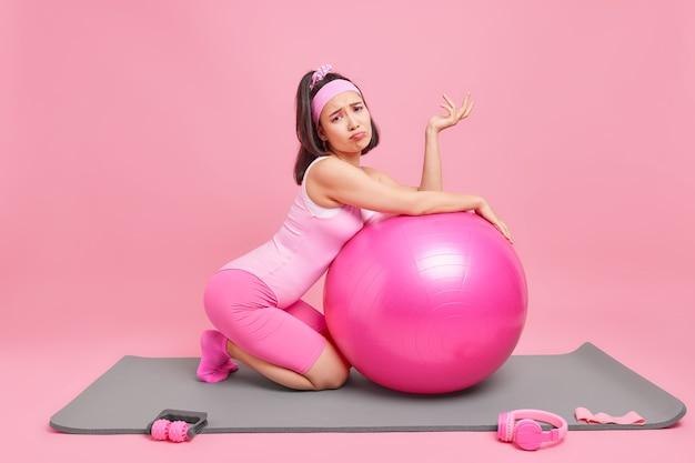 自宅でのトレーニングがピンクで隔離された周りのスポーツ用品とカレマットでアクティブワーヘッドバンドポーズを着用した後、女性はフィットネスボールに寄りかかって疲労感を感じる