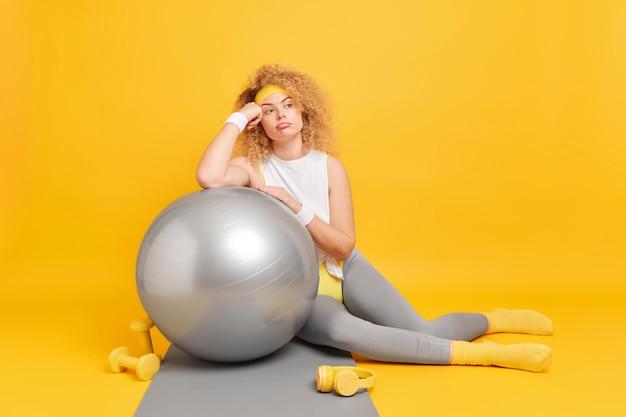 女性はフィットネスボールに寄りかかって、スポーツ用品に囲まれたアクティブウェアに身を包んだトレーニングやトレーニングをしています