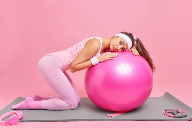 Woman leans at fitness ball has tired expression trains at home gym dressed in activewear poses on knees
