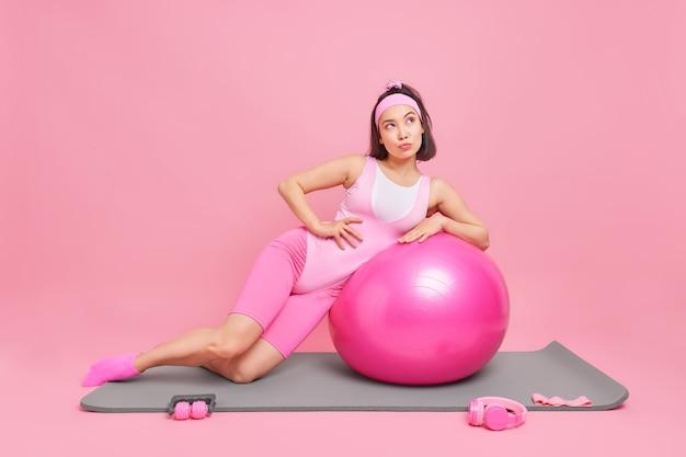 女性はピンクに分離された思考に深くあるカレマットにフィットネスボールのポーズに傾いています