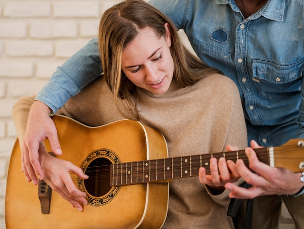 Woman learning how to play guitar with teacher at home