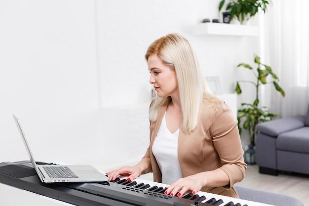Женщина учится играть на пианино дома, следуя онлайн-учебнику