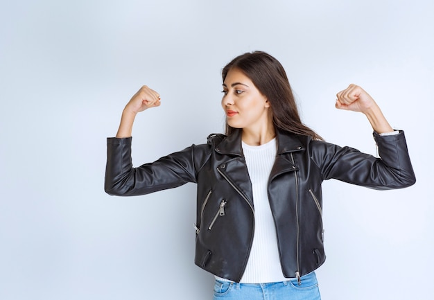Woman in leather jacket demonstrating her arm muscles.