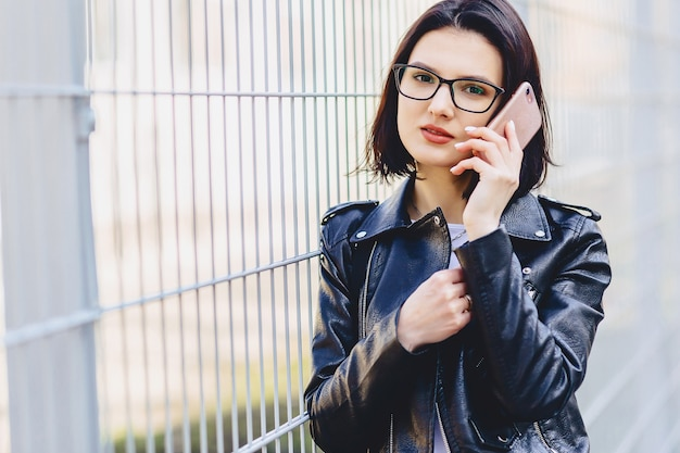 Woman in leather jacket in glasses talking on phone
