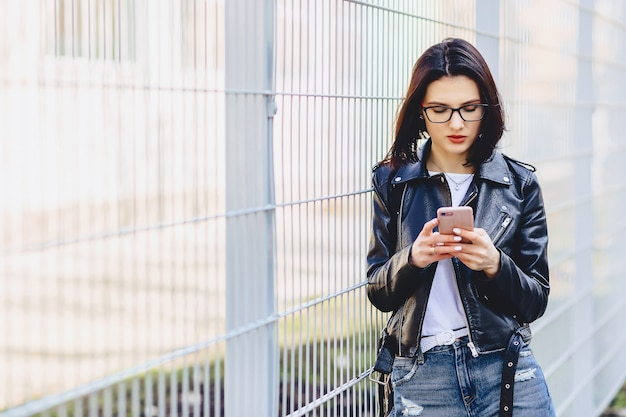 Woman in leather jacket messaging on phone at street