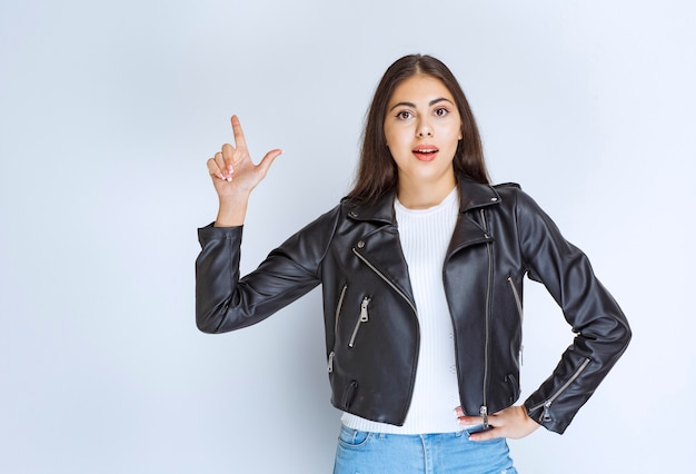 Woman in leather jacket pointing at something above.