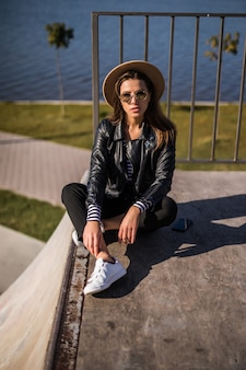Woman in leather jacket seat on the pier near the lake in cold sunny autumn day