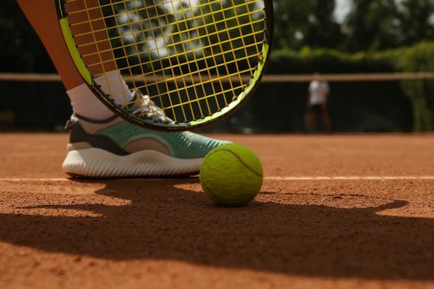 粘土のコートで女性の脚、ラケット、テニスボール