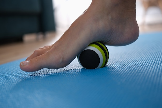Woman leg rolling ball on foot at home closeup