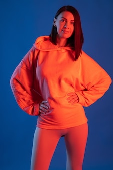 青い壁にオレンジ色の照明で女性のレギンスとパーカー