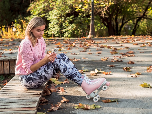 Woman in leggings and roller skates holding smartphone with copy space
