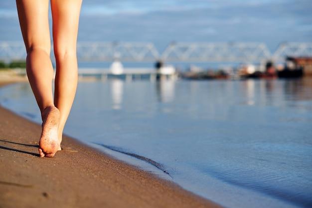 都市の背景に海の水とビーチの砂の上を歩く女性の足と足