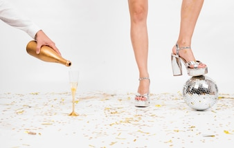 Woman legs and glassof champagne on floor