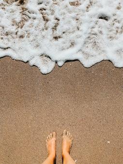 砂浜の夏の日の海の泡の波で裸足で女性の足。女性の足の上の上面図