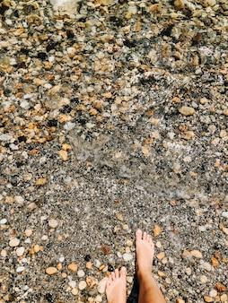 海の波で裸足で女性の足石の殻ビーチ夏の日。女性の足の上の上面図