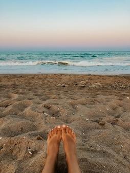 裸足の女性の足。海の青いアクアマリンの波の砂のビーチ。オーシャンフォーム。自然な背景の夕焼け空