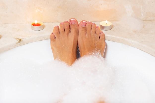 Woman legs in bath foam. relaxation in spa.