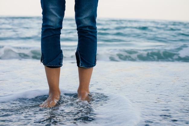 Woman legs in blue jeans standing in the sea water on the coast