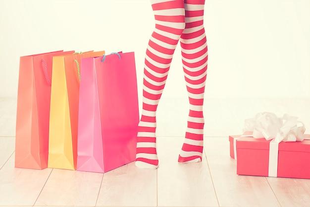 女性の足。クリスマスの買い物のコンセプト