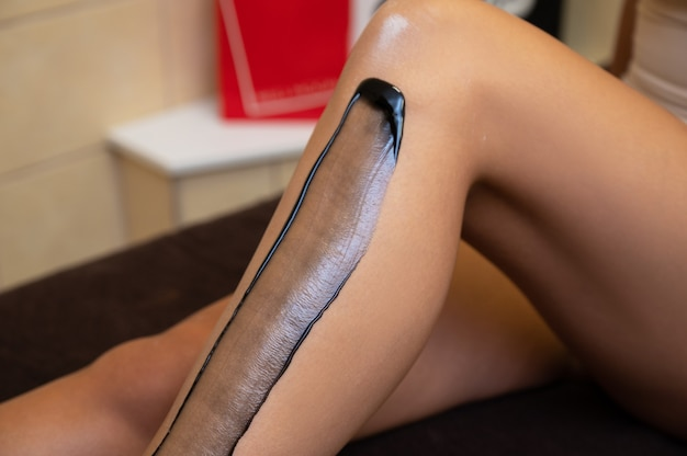 Woman legs closeup in beauty clinic ready for removing hair procedure using a black shugaring paste ...