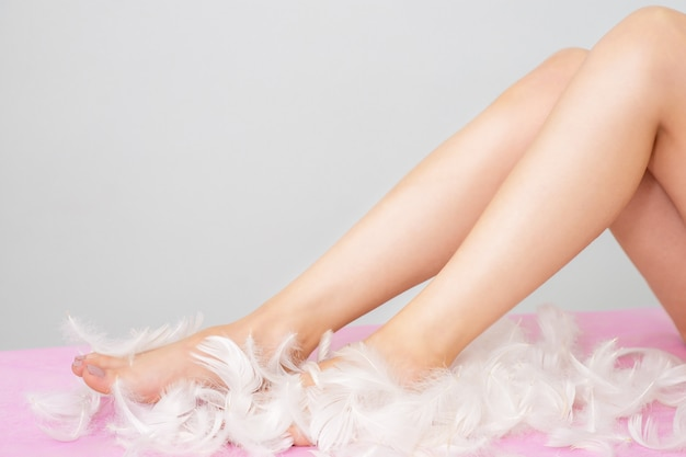 Woman legs in feathers with perfect hairless smooth and silky skin.