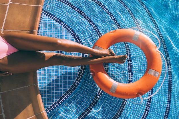 Женщина ноги в бассейне с спасателем