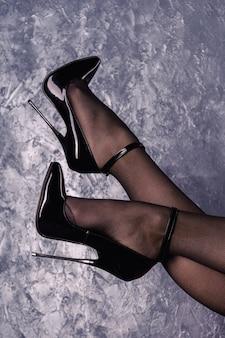 Женские ножки в черных фетишах на высоких каблуках из блестящей лакированной кожи на шпильках с ремешком на щиколотке у стены из венецианской лепнины