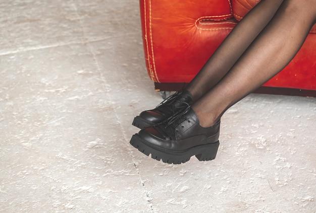 빨간 의자에 검은색 여자 다리. 레트로 스타일입니다. 팬티 스타킹 컨셉 사진에 글래머와 우아한 젊은 여성