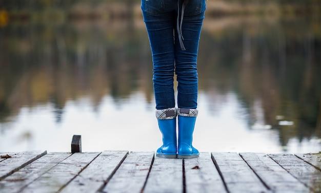 다리에 서있는 파란색 고무 부츠에 여자 다리