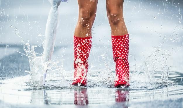 夏の春や秋の水たまりに傘がジャンプする点線の赤いゴム長靴の女性の足。