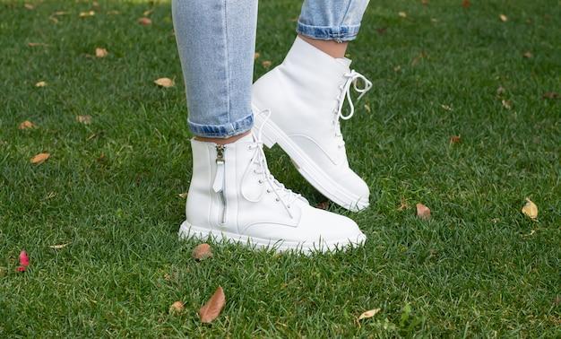 緑の草の上のファッショナブルな白いカジュアルブーツの女性の足
