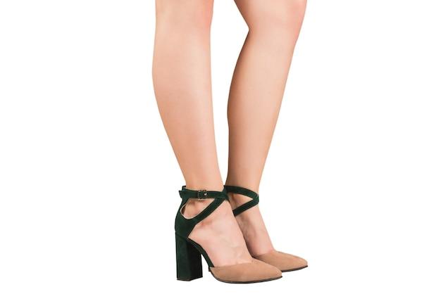 白で隔離されるかかとの緑とベージュのサンダルの女性の足