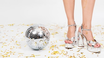 Woman legs in high heels and disco ball