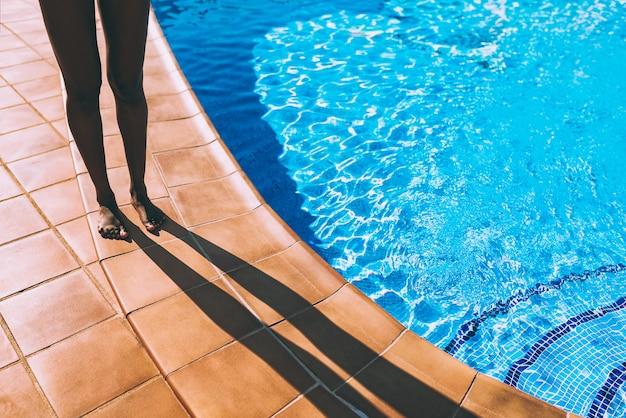 Ноги женщины делают тень у бассейна