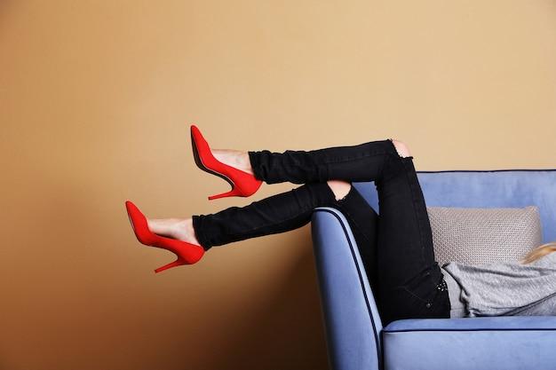部屋にスタイリッシュな靴を履いたソファの上の女性の足