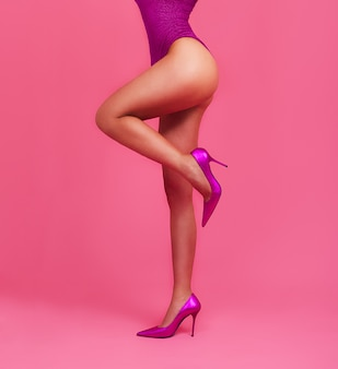 Woman legs on pastel pink color