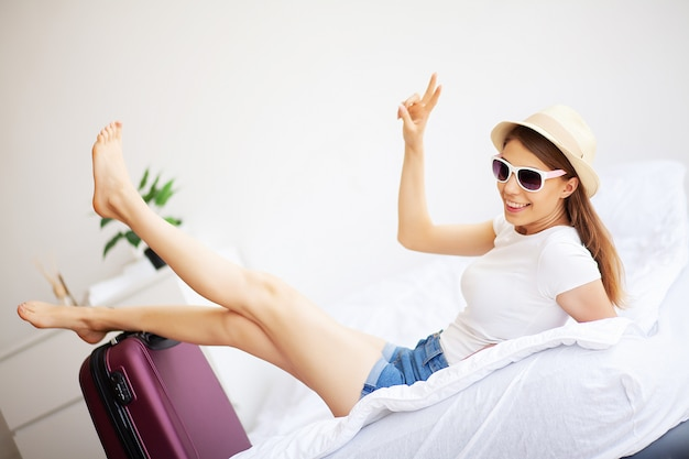 Woman legs raised up on the baggage, young woman at home laying in bed.