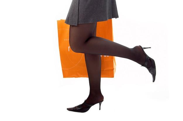 Ноги женщины бегают по магазинам с бумажным пакетом на белом