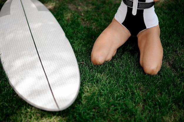 白いウェイクボードと緑の芝生に座っている女性の足